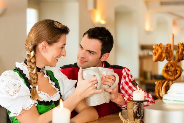 レストランやパブで伝統的なバイエルンtrachtの若いカップル