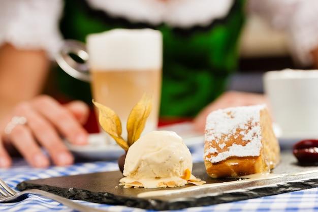 レストランやパブで伝統的なバイエルンtrachtの若い女性