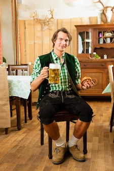 レストランやパブで伝統的なバイエルンtrachtの若い男