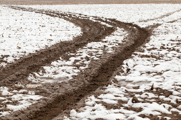通過する車から残っている雪を追跡して印刷します。冬の小さな田舎道。上から下にクローズアップされました。
