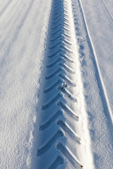 Track car wheel on the white real snow after snowfall. winter close-up.