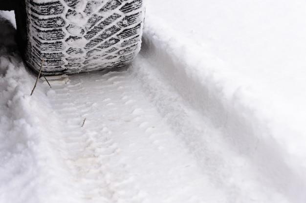 雪の上で車の車輪を追跡します。冬の道路の車のタイヤ。車の車輪からの痕跡。雪の上のタイヤ。