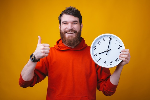Track your time, it flies. photo of a happy man showing thumb up and holding a white clock on yellow space.