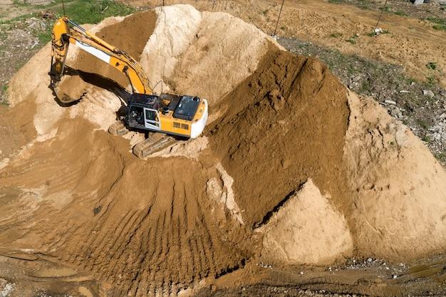Гусеничный экскаватор перегружает песок с насыпи.