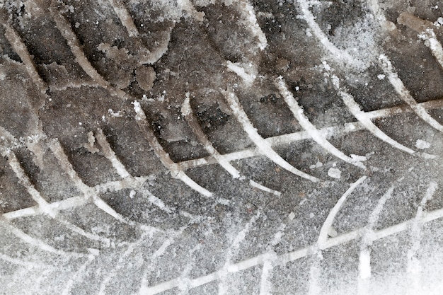 Tracks from the tread of a car tire in the snow during the winter season