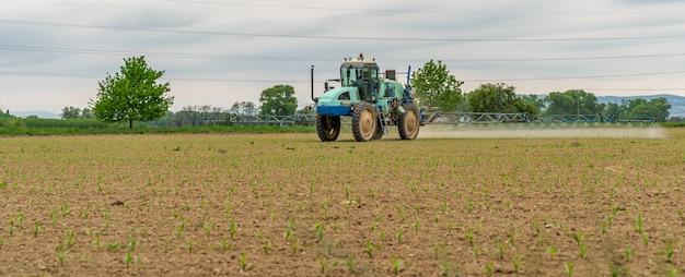 Трактор приспособлен для опрыскивания сорняков и вредителей в поле