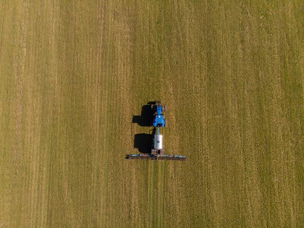 겨울 밀의 토양에 액체 미네랄 비료를 적용하는 트랙터