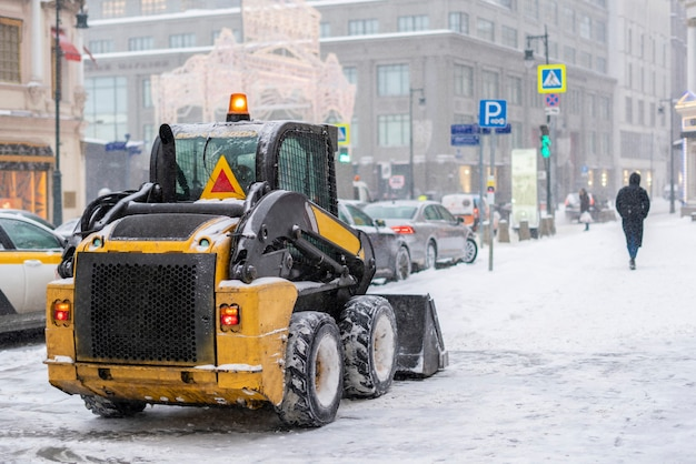 A tractor clean street from snow after a blizzard b