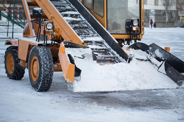 Tractor cleaning the road from the snow. excavator cleans the streets of large amounts of snow in city.