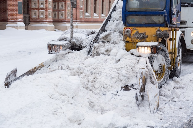 Tractor cleaning the streets of large amounts of snow in city after snowstorm.