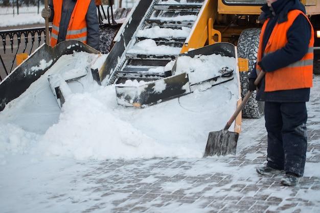 눈에서 도로를 청소하는 트랙터. 굴착기는 도시의 많은 양의 눈 거리를 청소합니다. 노동자들은 겨울에 도로에서 눈을 쓸고, 눈 폭풍에서 도로를 청소합니다.