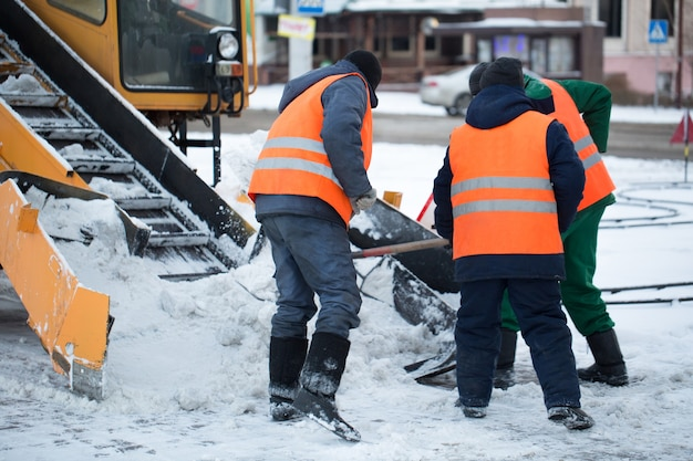 눈에서 도로를 청소하는 트랙터. 굴삭기는 도시의 많은 양의 눈으로 거리를 청소합니다. 노동자들은 겨울에 도로에서 눈을 쓸어 버립니다.