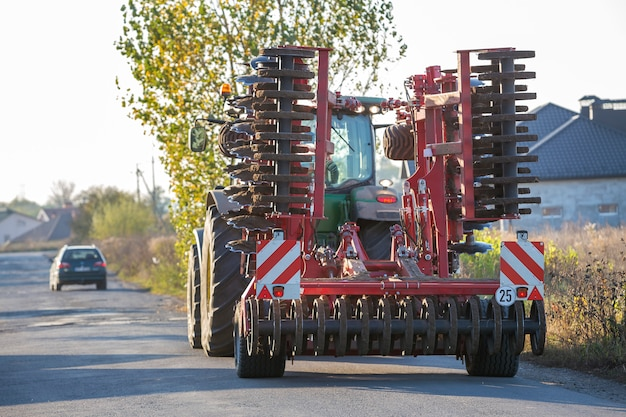 Tractor combine with disc harrows driving along rural road on sunny day.