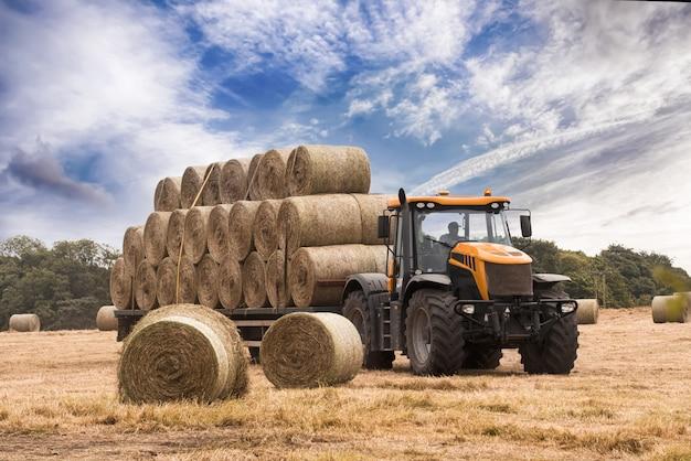 トラクターは夏に青い曇り空を背景に干し草を刈る
