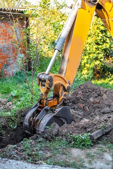 A tractor digs a trench with a bucket to lay a water supply system. preparation for laying water pipes in a country house.
