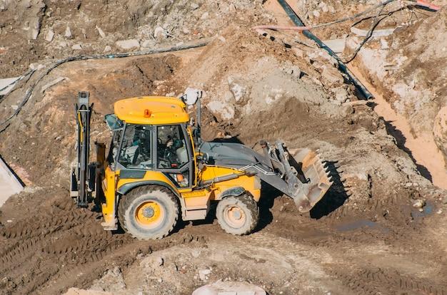 Трактор-экскаватор с ковшом проезжает по грязевым землям, вид с высоты.