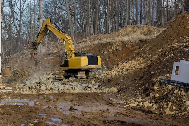 山の建設現場で大きな石を砕くトラクターが働いています