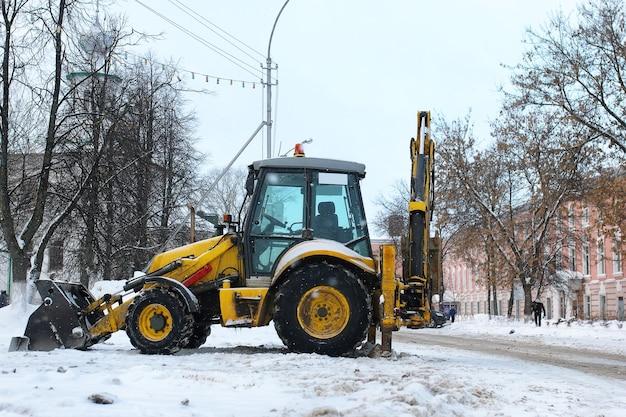 퇴근 후 도시 거리에 제설용 트랙터가 주차되어 있다
