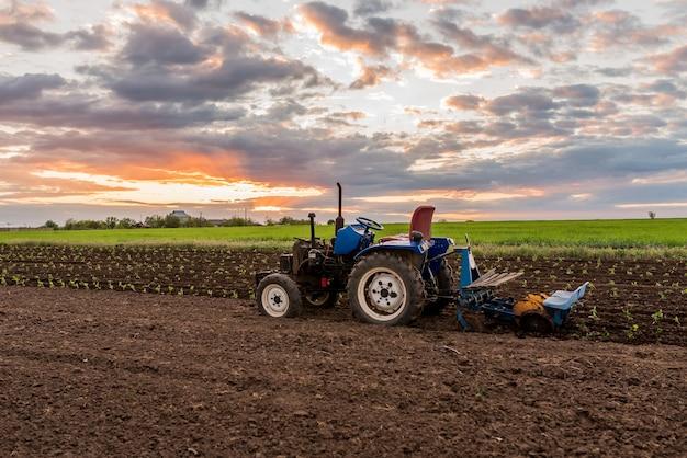 Трактор посреди поля на закате сельский пейзаж крупным планом