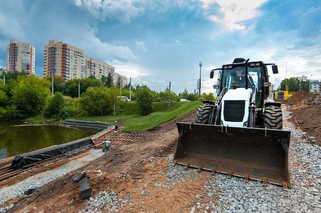 Трактор летом выравнивает землю на стройплощадке