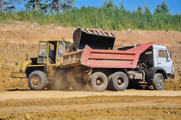 The tractor loads the soil into the dump truck road repairs