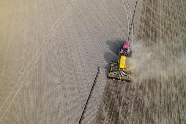 Трактор на вспаханном поле, вид сверху. сельскохозяйственное поле для посадки овощей. трактор делает борозды на поле.