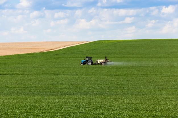 농약을 취급하는 동안 농업 분야에서 촬영 된 트랙터. 구름과 하늘