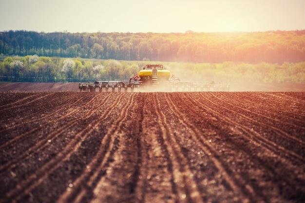 Трактор вспахивает поле фермы в рамках подготовки к весенней посадке