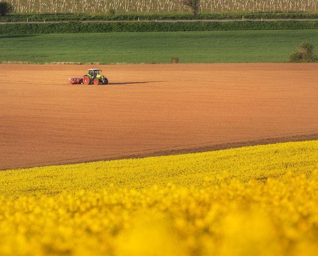 Tractor plowing a field in south moravia at sunset