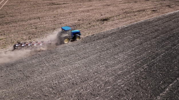 Tractor plowing field top view, aerial photography with drone