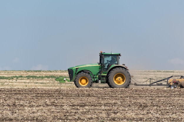 Tractor plowing the ground against the blue sky