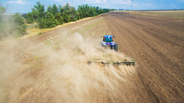 A tractor plowing and sowing in field