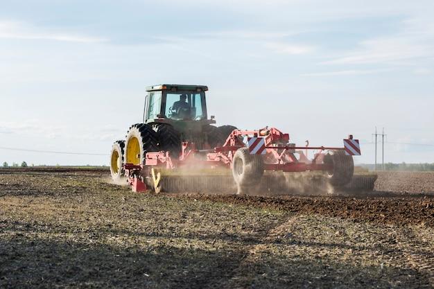 Трактор пашет землю в поле