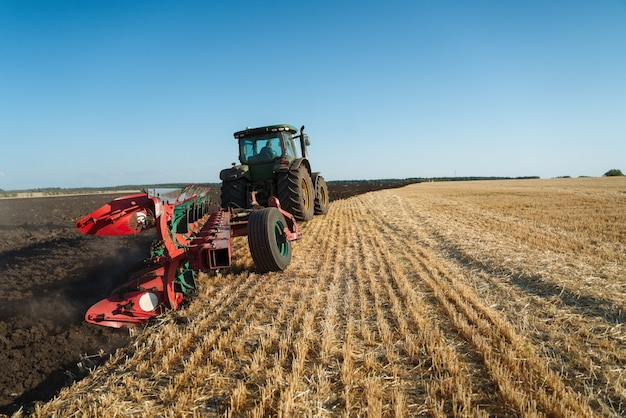 The tractor plows the land agriculture image