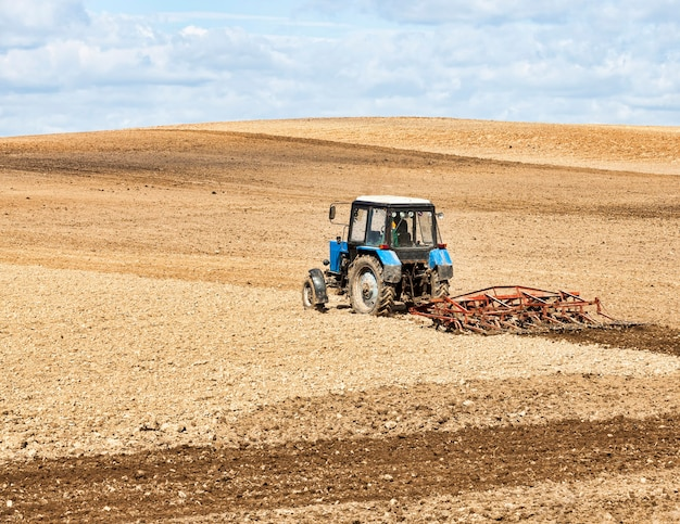 Tractor plows the soil in a field