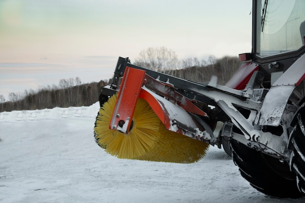Tractor removes snow from the road in winter