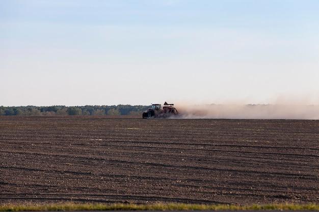 트랙터는 들판을 가로 질러 땅을 일하며 큰 수확물을 생산합니다. 백그라운드에서 사진, 푸른 하늘입니다. 먼지와 모래를 날리는 트랙터 용