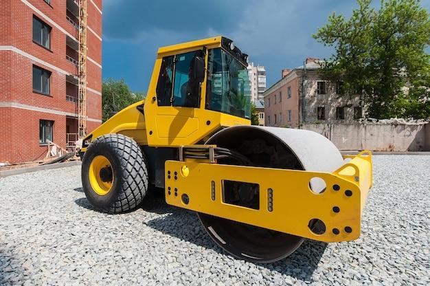 Каток трактора уплотняет почву для строительства новой дороги