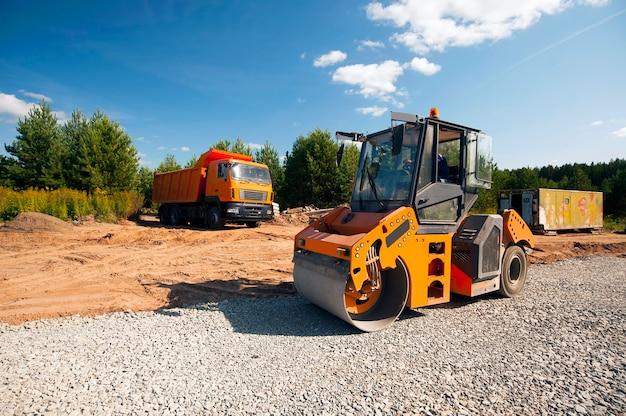 Тракторный каток уплотняет почву новой дороги