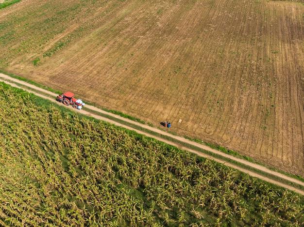 Tractor running through empty crop field