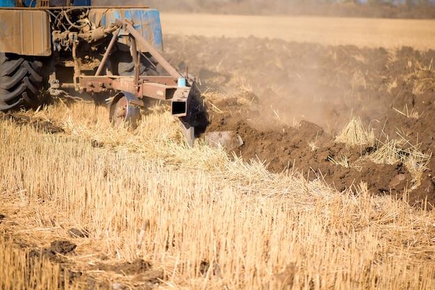 트랙터는 가을 날 푸른 하늘과 함께 수확 후 그루터기에 직접 파종합니다.