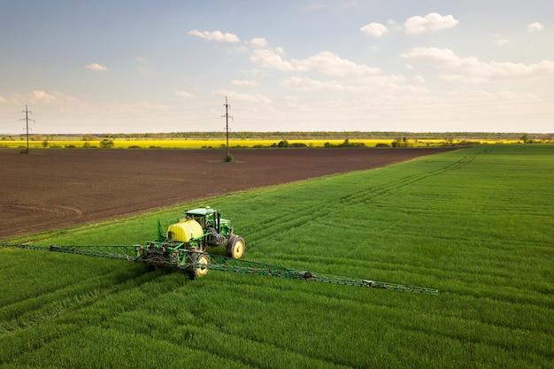 Трактор распыляет химические пестициды с помощью опрыскивателя на большом зеленом сельскохозяйственном поле весной.