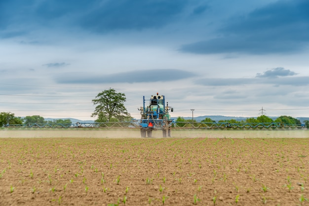 Трактор распыляет химикаты на поле для лучшего сбора урожая и борьбы с вредителями. копировать пространство