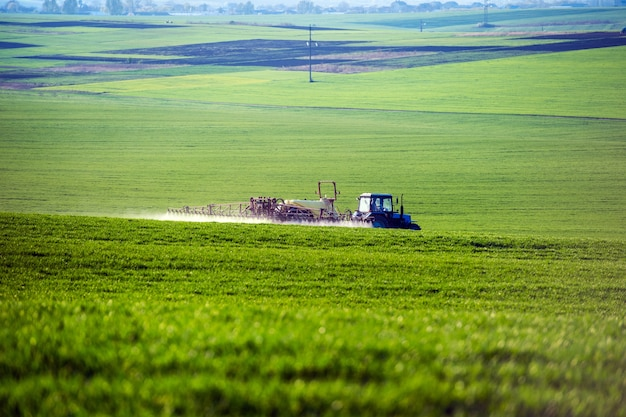 Трактор распыляет пестициды на поле с опрыскивателем летом