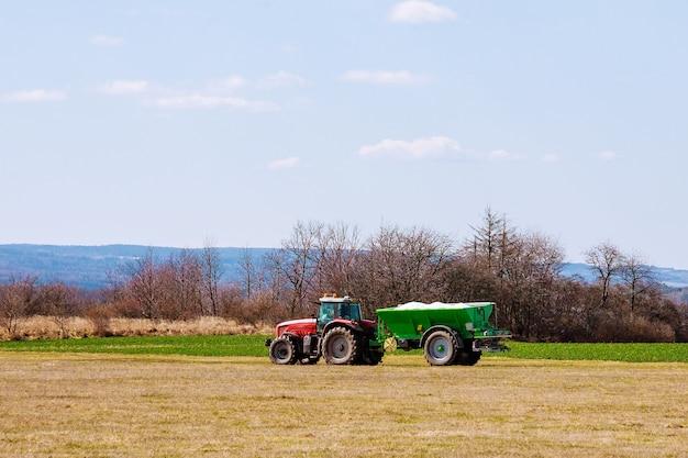 Трактор разбрасывает удобрения на траве поля. сельскохозяйственные работы.