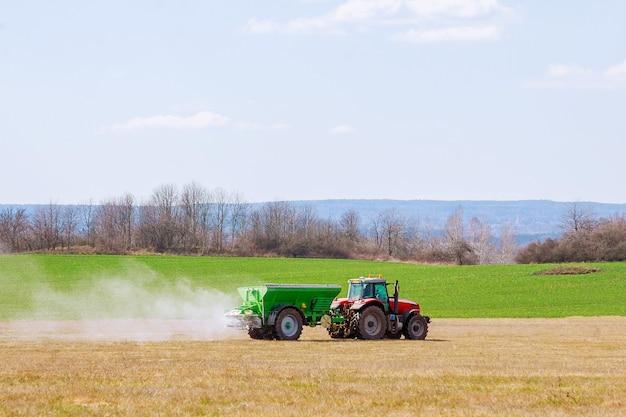 芝生のフィールドに肥料を散布するトラクター。