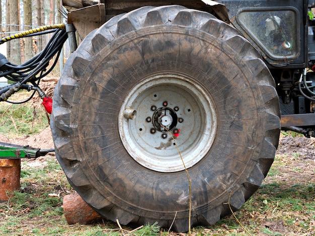쓰러진 나무를 수집하는 트랙터는 바퀴를 닫고 옆으로 서 있습니다.