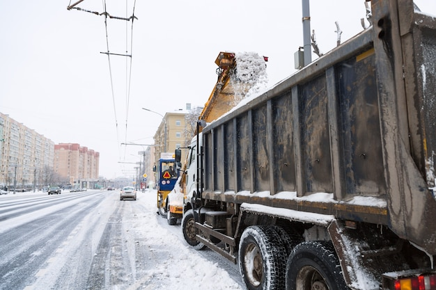 Tractor and tipper car cleaning the streets of large amounts of snow in city after snowstorm