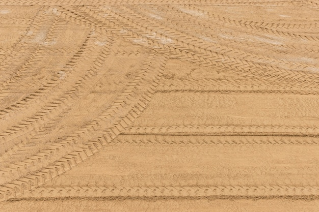 Tractor tire tracks on the sand after cleaning up.