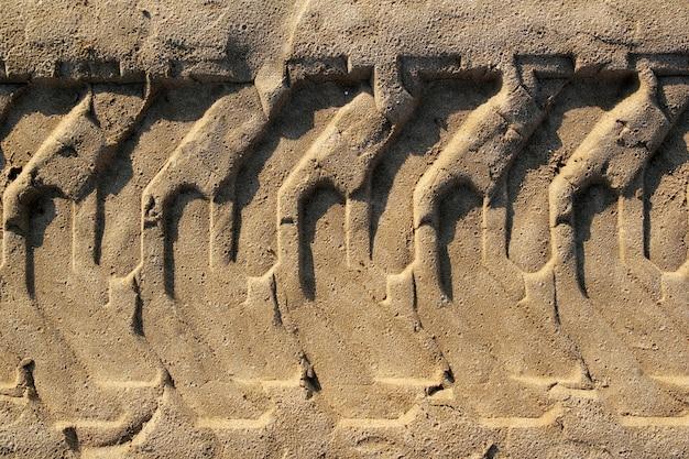 ビーチの砂の上に印刷されたトラクタータイヤ足のフットプリント